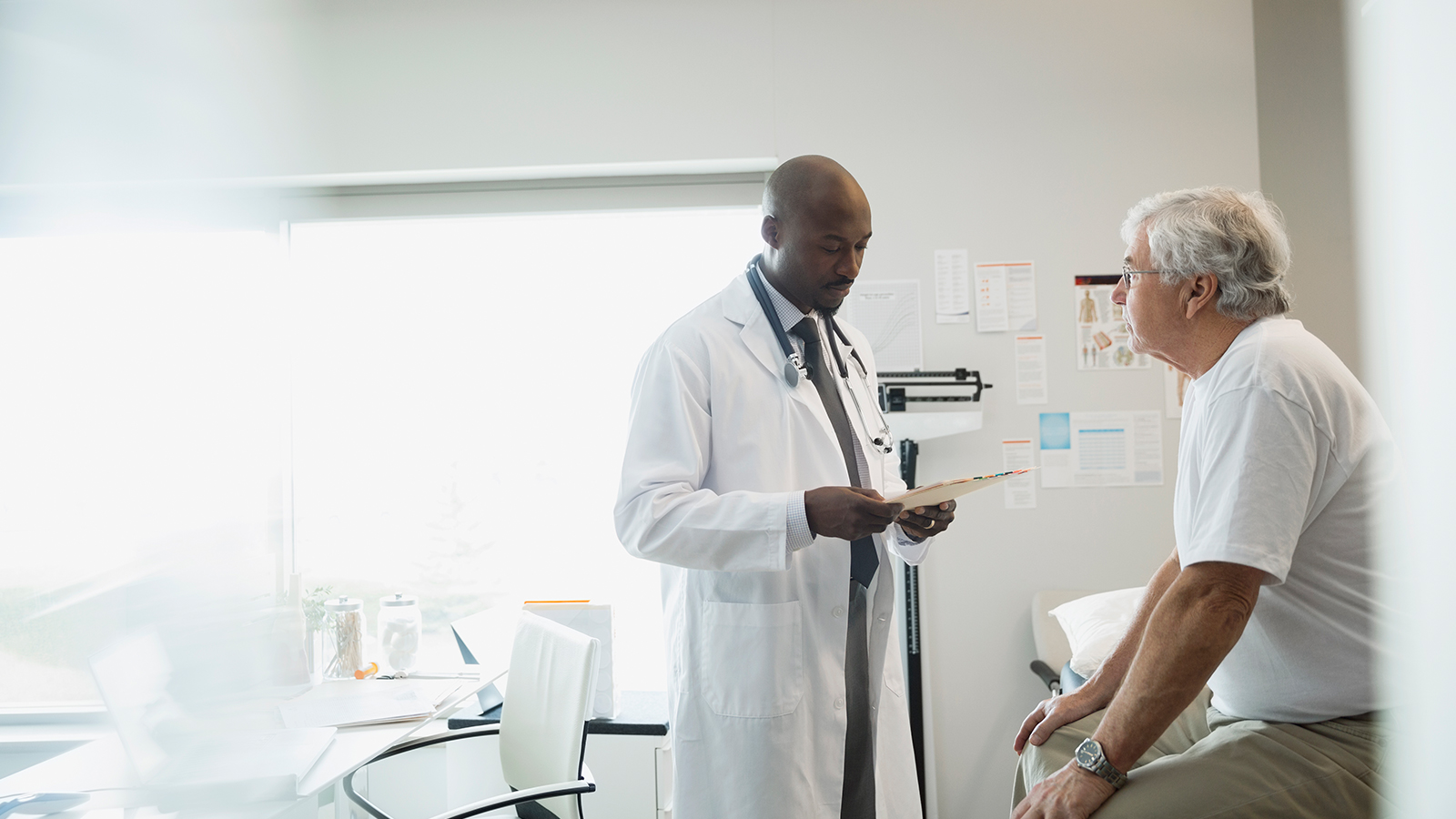 Doctor standing and speaking to a sitting patient in a hospital room.