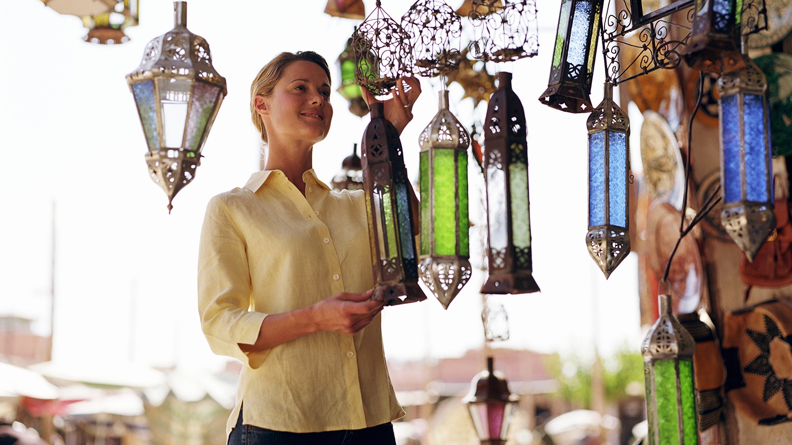 Young woman admiring lanterns hanging in front of a store.