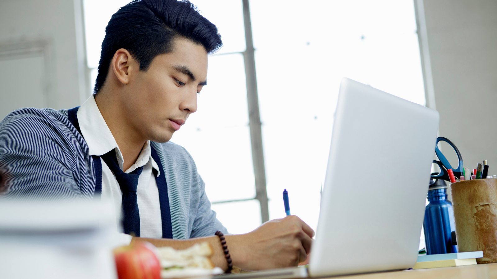 Young man sitting at his desk and working in front of his laptop.