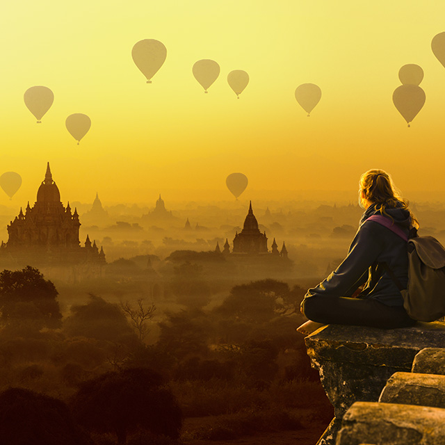 Tourist girl and hot air balloons in Bagan, Myanmar