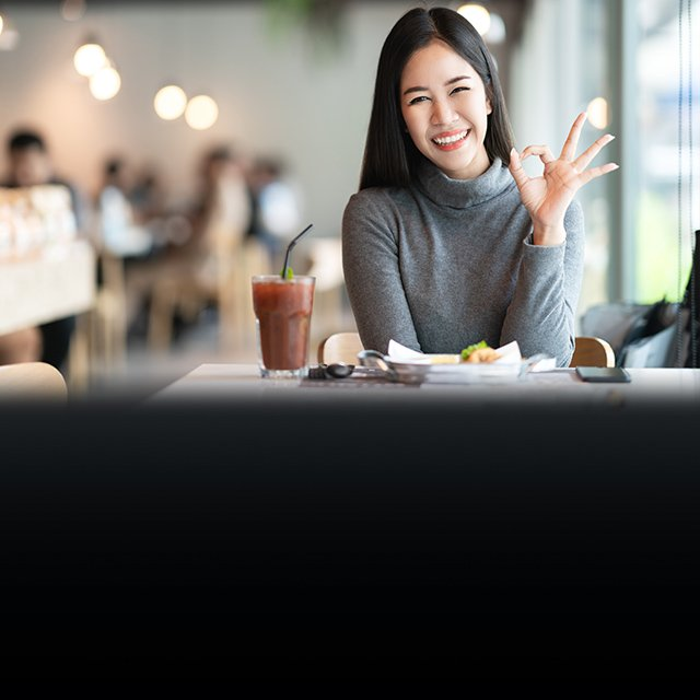 female smiling hand making ok sign in a cafe