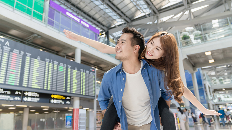 Happy young asian couples traveler having fun at airport terminal. Travel and lover concept.